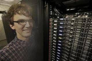 In this Wednesday, June 22, 2016, photo, Massachusetts Institute of Technology researcher Carl Vondrick looks through a protective door while standing next to a computer server cluster, right, on the MIT campus, in Cambridge, Mass. MIT says a computer that binge-watched TV shows such as 'The Office,' 'Big Bang Theory' and 'Desperate Housewives' learned how to predict whether the actors were about to hug, kiss, shake hands or slap high-fives, a breakthrough that eventually could help the next generation of artificial intelligence function less clumsily.