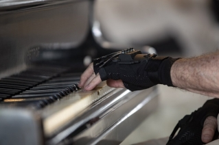Brazilian pianist Joao Carlos Martins plays the piano wearing bionic gloves at his home in Sao Paulo, Brazil, Wednesday, Jan. 22, 2020. Martins, 79, was for decades Brazil's most acclaimed pianist, but an accident an a degenerative disease forced him to stop playing with both hands since 1998. That changed a few months ago when a new friend came to him with a pair bionic gloves that suit him perfectly. He can now play again with nine out of ten fingers.