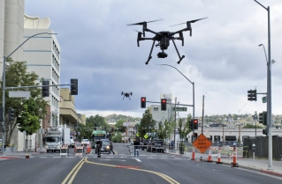 In this May 21, 2019 photo, two drones fly above Lake Street in downtown Reno, Nev., on, as part of a NASA simulation to test emerging technology that someday will be used to manage travel of hundreds of thousands of commercial, unmanned aerial vehicles (UAVs) delivering packages. It marked the first time such tests have been conducted in an urban setting.