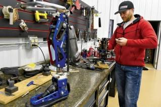 This Dec. 22, 2017, file photo features Mike Schultz during his preparation to compete in the 2018 Winter Paralympics in South Korea. The owner of BioDapt, he's shown here working on a performance prosthetic for an athlete in his shop in St. Cloud, Minn.