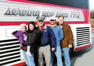 Cyr employees and family members pose in front of one of the company's motor coaches. Left to right are Bookkeeper Becky Whitmore, her daughter Ruby, Company President Joe Cyr, IT expert Mike Cyr, and body work & painter Peter Cyr.