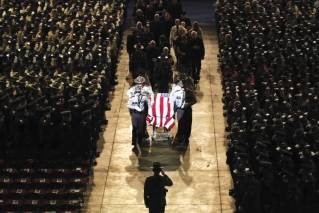 Pallbearers walk alongside the casket of Cpl. Eugene Cole at the conclusion of the funeral service at the Cross Insurance Center, Monday, May 7, 2018, in Bangor, Maine. Cole, a sheriff's deputy, was the first officer to be killed in the line of duty in Maine in nearly 30 years when he was killed early on April 25 in Norridgewock.