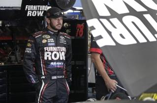 Martin Truex Jr. watches as his crew works on his car before practice for Saturday's NASCAR Sprint Cup series auto race at Charlotte Motor Speedway.