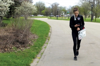 In this May 11, 2019 photo, Emily Mogavero, 17, looks at her cellphone while walking in Delaware Park in Buffalo, N.Y. The teenager said keeping up with social media and maintaining online profiles can make her stress levels rise but will put her phone out of reach or power it down to manage it.