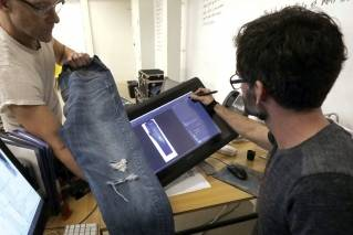 In this Feb. 9, 2018, photo, Bart Sights, head of the Eureka Lab, left, and Aykut Aygun, manager of technical innovation, give a demonstration on designing jeans at Levi's innovation lab in San Francisco. The process of making and selling an item of clothing is speeding up, as shoppers want products faster and faster in the age of Amazon. Companies like Tommy Hilfiger and Levi Strauss are digitizing different steps, like creating digital showrooms for buyers who place orders based on computerized rendering of a garment or producing 3D samples that are emailed to factories, instead of waiting for a physical prototype.
