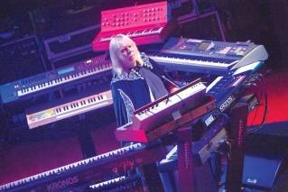 "Rick Wakeman wearing his familiar cape, standing amongst his iconic keyboards during the 2017 tour ""YES featuring Jon Anderson, Trevor Rabin and Rick Wakeman."""