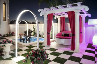 This 2019 photo provided by Ryan Hughes of Ryan Hughes Design Build shows an outdoor space at a home in Florida. Tampa-based designer Hughes took inspiration from the homeowner's daughter's love of Alice in Wonderland to create a playful, over-the-top outdoor space complete with unique lighting effects, a hanging bed and oversized checkerboard.