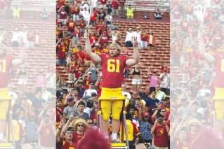 Southern California long snapper Jake Olson leads the USC Trojan Marching Band following an NCAA college football game against Western Michigan, Saturday, Sept. 2, 2017, in Los Angeles. Olson lost his sight eight years ago to a rare form of retinal cancer, but joined the USC team on a scholarship for disabled athletes and began practicing with the Trojans 2 years ago.