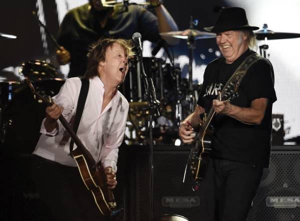 Paul McCartney, left, is joined by Neil Young during his performance on day 2 of the 2016 Desert Trip music festival at Empire Polo Field on Saturday, Oct. 8, 2016, in Indio, Calif.
