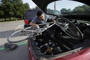 In this Thursday, June 23, 2016 photo William Spiro, of Newton, Mass., removes his bike from his car at a Park & Pedal area in a parking lot, in Boston, as he prepares to complete his morning commute. The recently expanded Park & Pedal program offers motorists a chance to park their cars for free and then bike the rest of the way to work.