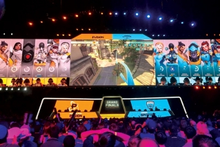 In this Friday, July 27, 2018 photo, fans watch the Philadelphia Fusion and London Spitfire compete in the Overwatch League Grand Finals' first night of competition at the Barclays Center in the Brooklyn borough of New York. The Overwatch League is making a grand gamble: that its deep pockets and massive infrastructure can keep it atop the esports mountain even as Fortnite comes charging for the crown.