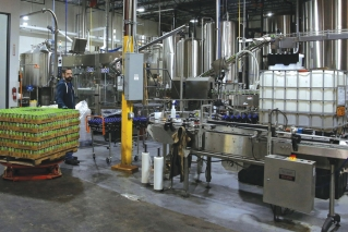 Josh Yager transfers cans of F5, one of their most popular brews, from the production line at COOP Ale Works in Oklahoma City, Friday, Jan. 18, 2019. COOP Ale Works, which distributes in six states including Oklahoma and Kansas, has discontinued two of its three 3.2 percent brews.