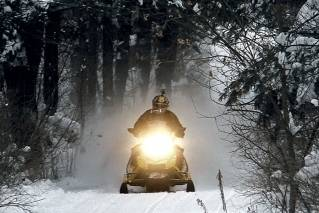 In this Dec. 31, 2012 file photo, a snowmobile travels a newly-groomed trail in East Montpelier, Vt. With plenty of fresh snow covering much of northern New England, the 2017 winter snowmobile season is off to a good start.