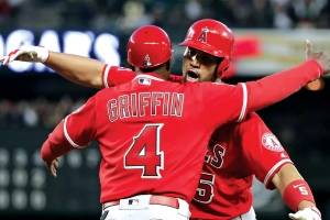 Albert Pujols (right) embraces first base coach Alfredo Griffin after hitting a single against the Mariners' Mike Leake in the fifth inning on May 4 for his 3,000th career hit.