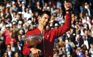 Novak Djokovic acknowledges the spectators' cheers at Roland Garros after winning the French Open on Sunday. (Michel Euler / Associated Press)