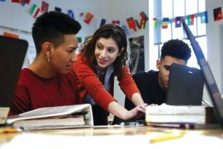 Sirio Chavez, left, and Anton Eiss, right, work with teacher Phoebe Sherman on the civics computer game iCivics during Sherman's 11th grade social studies class at Roosevelt High School's International Academy in Washington, Thursday, Nov. 16, 2017. Supreme Court Justice Sonia Sotomayor and former Supreme Court Justice Sandra Day O'Connor are backing iCivics that is now being translated into Spanish.