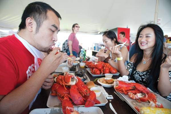 In this file photo from Aug. 3, 2016, members of a Japanese travel TV show eat lobster at the 69th Maine Lobster Festival as they wrap up the day's shoot in Rockland.