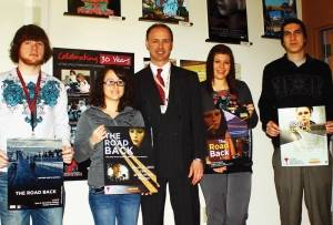 "Acadia Hospital Communications Officer (Center) Alan Comeau is joined by NESCom graphic design students (L-R) Ben Hatch, Kiera Plante, Mary Webber and David Conant who display their poster designs for the film, ""The Road Back."""