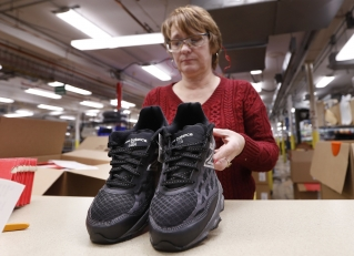 In this Monday, Dec. 17, 2018 photo, Ruby Williams inspects a pair of running shoes designed for the military and manufactured at the New Balance factory in Norridgewock. The new contract fulfills a requirement for new military recruits to receive American-made apparel.
