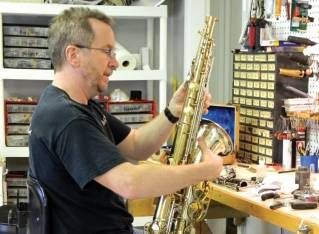 Bangor Brass & Woodwind Repair owner Joe Shaw repairs a saxophone inside his new business on Hammond St.