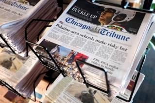 In this Monday, April 25, 2016, file photo, Chicago Tribune and other newspapers are displayed at Chicago's O'Hare International Airport. Tribune Publishing is fighting to stave off USA Today owner Gannett, though its not immediately clear why. Print ad revenues are in the toilet and cost-cutting is the mantra of the day. It may all come down to a clash of bean-counters against visionaries, or maybe Tribune is just holding out for the best possible price. (AP file photo/Kiichiro Sato)