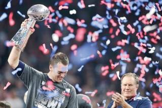 New England Patriots quarterback Tom Brady hoists the Vince Lombardi Trophy while coach Bill Belichick looks on after the Patriots won Super Bowl LI.