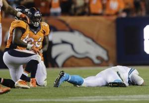 Carolina Panthers quarterback Cam Newton  lies on the turf after a roughing the passer penalty on Denver Broncos free safety Darian Stewart, No. 26, on Sept. 8, 2016, in Denver.