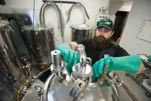 Marsh Island brewmaster Clay Randall prepares brewing equipment at the brewery's Orono location, a former car repair garage, on Thursday, Sept. 22, 2016.