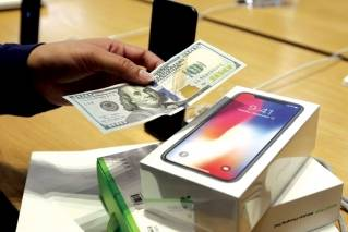 In this photo, a customer hands over cash as she pays for an iPhone X at the Apple Store on New York's Fifth Avenue. Apple is facing some thorny questions about its best-selling product, with conspiracy theories swirling around its secret slowdown of older iPhones and a cloud of uncertainty hanging over its big bet on the high-priced iPhone X.