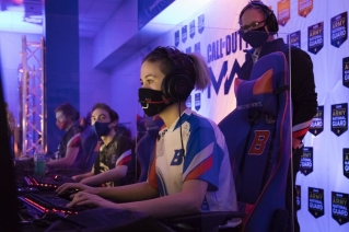 "Boise State esports coach Doc Haskell, right, watches scholarship graduate student Artie ""N3rdybird"" Rainn compete in a match in Boise, Idaho, on Thursday, March 4, 2021. Colleges and universities rushing to invest in the booming arena of varsity esports are overwhelmingly committing opportunities and scholarships to male players, according to data collected by The Associated Press. Boise State was among the more equal schools in the AP's survey, with 16 male players, five female players and three who identified as nonbinary."