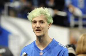 "In this Sept. 10, 2018, file photo, Fortnite superstar Tyler ""Ninja"" Blevins watches before an NFL football game between the Detroit Lions and New York Jets in Detroit. Blevins is leaving Twitch and taking his video game live streams to Microsoft's Mixer platform, a stunning transition that could have wide-ranging consequences for the rapidly growing industry. Blevins announced his move Thursday, Aug. 1, 2019, ending a hugely profitable partnership with Twitch, a live streaming giant owned by Amazon."