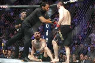 Khabib Nurmagomedov, right, is held back by referee Herb Dean after fighting Conor McGregor, bottom, during a lightweight title mixed martial arts bout at UFC 229 in Las Vegas, Saturday, Oct. 6, 2018. Nurmagomedov won the fight by submission during the fourth round to retain the title.