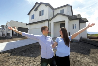 In this April 27, 2019, photo, Andy and Stacie Proctor stand in front of their new home in Vineyard, Utah. For some millennials looking to buy their first home, the hunt feels like a race against the clock. The Proctors ultimately made a successful offer on a three-bedroom house for $438,000 in Vineyard.
