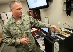MSgt. Jason Howes, of Bucksport, displays parts that the 101st Air Refueling Wing's machine shop has had to recreate. Howes, who oversees the shop, said their new 3-D polymer printer is certified to craft such parts, and since the KC-135s are older, the parts must often be manufactured on base since Boeing, the plane's manufacturer, no longer produces or stores them.