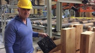 In this Nov. 11, 2016 photo, John Redfield, chief operating officer of D.R. Johnson Lumber Co. in Riddle, Ore., poses for a photo as he shows an example of a cross-laminated timber, or CLT, panel that underwent a flammability test. D.R. Johnson is one of just two companies in the United States currently able to produce CLT panels.