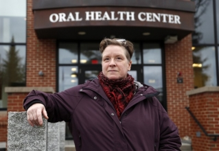 In this Wednesday, April 24, 2019 photo, Ebyn Moss poses for a photo outside the University of New England's dental school in Portland, Maine. Moss has made the two-hour drive several times from her home in Troy, Maine, for extensive treatment at the dental school after breaking a tooth below the gum line in 2017. She said a dental therapist nearby her home would have made preventive care easier in the first place. Several states have recently pass laws authorizing dental therapists, which perform basic procedures and leave the more complex work to dentists.