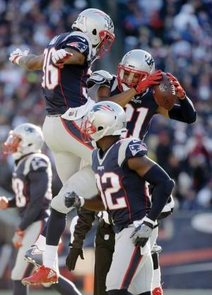 New England Patriots cornerback Malcolm Butler, top right, celebrates his interception with Brandon King, left, during the first half of an NFL football game against the Los Angeles Rams, Sunday, Dec. 4, 2016, in Foxborough, Mass.