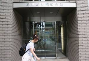 A woman walks past Funai Electric CO, LTD in Tokyo, Monday, July 25, 2016. Japanese electronics maker Funai Electric Co. says it's yanking the plug on the world's last video cassette recorder. A company spokesman, who requested anonymity citing company practice, confirmed Monday that production will end sometime this month, although he would not give a date.