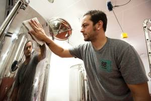 Bangor Beer Company brewmaster Jared Lambert cleans a tank in the brewing space of the new brewery.