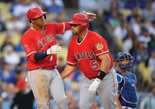 Albert Pujols, center, congratulated by a teammate during an April exhibition game.