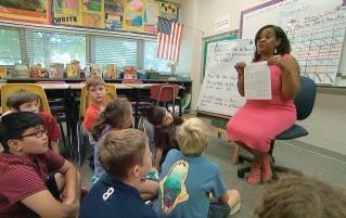 In this Tuesday, Sept. 13, 2016 still image from video, Kimberly Coleman-Mitchell, right, teaches her fourth grade class at Oakridge Elementary School in Arlington, Va. Elementary schools in Arlington, South Burlington, Vt., and Holyoke, Mass., are among those that went homework-free at the start of the school year.