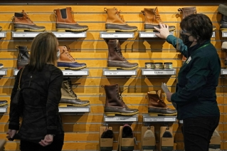 A salesperson helps a customer shopping for Bean Boots at the L.L. Bean flagship retail store, Thursday, March 18, 2021, in Freeport, Maine. Maine-based retailer L.L. Bean saw the best sales in nearly a decade during pandemic. Officials say the Freeport-based retailer started its fiscal year with store closings and worries about survival but the company weathered the turbulent times to revenue growth of 5%.