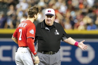 In this May 13, 2018, file photo, MLB umpire Joe West, right, talks with a player in the ninth inning during a baseball game between the Arizona Diamondbacks and the Washington Nationals in Phoenix. West, who has umpired more than 5,000 big league games, said the 2016 TrackMan computer system test was far from perfect.