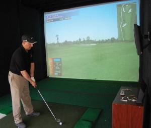 Robert Budge gets set to tee off on a par 3 hole while playing indoor golf at Traditions in Holden.