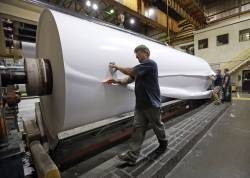 In this Monday, Nov. 10, 2014, file photo, workers cut a sample section off a large roll of paper made at the Sappi Paper Mill in Skowhegan, Maine. The death of Maine's paper industry, once a point of entry to the middle class for thousands, accelerated when the mills in Millinocket and Bucksport closed that same year.
