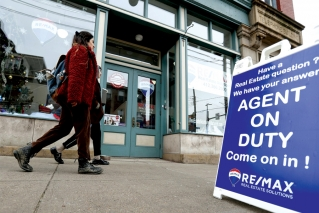 In this Jan. 4, 2019, file photo people walk by a real estate office in Pittsburgh's Lawrenceville neighborhood. Buying a home for the first time is challenging no matter your marital status. But doing so in an unmarried partnership poses unique challenges.