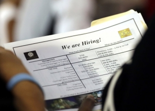 In this June 21, 2018 file photo, a job applicant looks at job listings for the Riverside Hotel at a job fair hosted by Job News South Florida, in Sunrise, Fla. The U.S. unemployment rate fell to 3.7 percent in September 2018 the lowest level since December 1969 — signaling how the longest streak of hiring on record has put millions of Americans back to work. Employers added just 134,000 jobs last month, the fewest in a year, the Labor Department said Friday, Oct. 5. But that figure was likely depressed by the impact of Hurricane Florence.