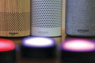 In this Wednesday, Sept. 27, 2017 file photo, Amazon Echo and Echo Plus devices, behind, sit near illuminated Echo Button devices during an event announcing several new Amazon products by the company in Seattle. As people get voice-activated speakers and online security cameras for convenience and peace of mind, are they also giving hackers a key to their homes? Many devices from reputable manufacturers have safeguards built in, but safeguards aren't the same as guarantees.