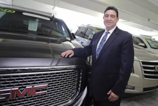 This photo taken Wednesday, Aug. 30, 2017, general sales manager Beny Ledesma poses for a photo at Williamson Cadillac Buick GMC dealership in Miami. If you're willing to fly, you can save when you buy. Perhaps thousands of dollars on a used SUV, car or truck. Used vehicle prices vary wildly between U.S. metro areas, sometimes over $3,000. So with some careful research and a plane ticket, it might be worth the time it takes to travel.