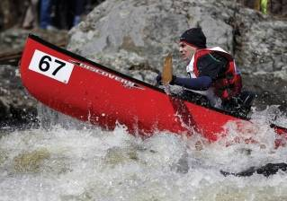 A member of David Naughton's team from Amherst, Mass., braces as his canoe bounces through Six Mile Falls during the 50th Kenduskeag Stream Canoe Race on Saturday, April 16, 2016, in Bangor.
